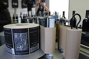 Machine labeling, machine applying a roll of wine labels